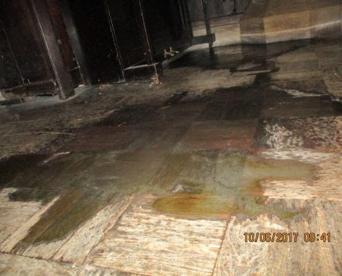 Close up of rain water on choir vestry's wooden floor